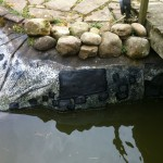 Repaired koi pond by bridge